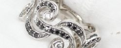 "A black and white diamond eternity ring of ""S"" scroll design to an 18ct white gold setting approximately 7.5 grams"