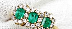An emerald and diamond ring, set with three emerald cut emeralds surrounded by round brilliant cut diamonds to an 18ct yellow gold setting and shank